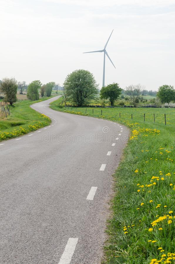 Wind turbine by a winding country road royalty free stock photos