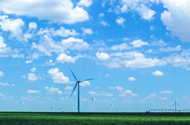 Wind turbines in agricultural field on Plains under beautiful blue cloudy sky with irrigation equipment in distance - selective. Focus royalty free stock images