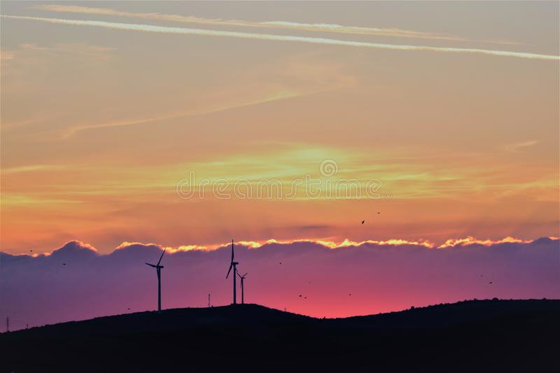 Wind turbines and beautiful colorful sunset and mountains royalty free stock photography