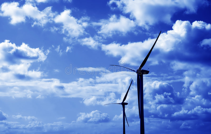 Wind turbines blue tint. Two wind turbines against fluffy clouds, blue tint over royalty free stock photography