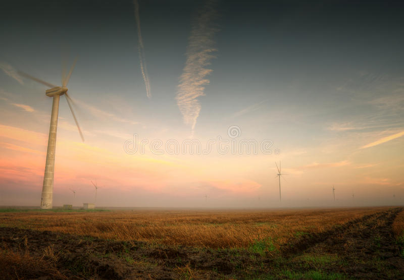 Wind turbines captured near cape Kaliakra, Bulgaria. With harvested wheat field. Sunrise and interesting clouds. A very beautiful combination of colors and stock photos