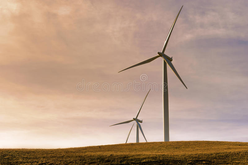 Wind Turbines in the Columbia River Gorge. Setting sunlight and two wind turbines on top of a hill in the Columbia River Gorge royalty free stock images