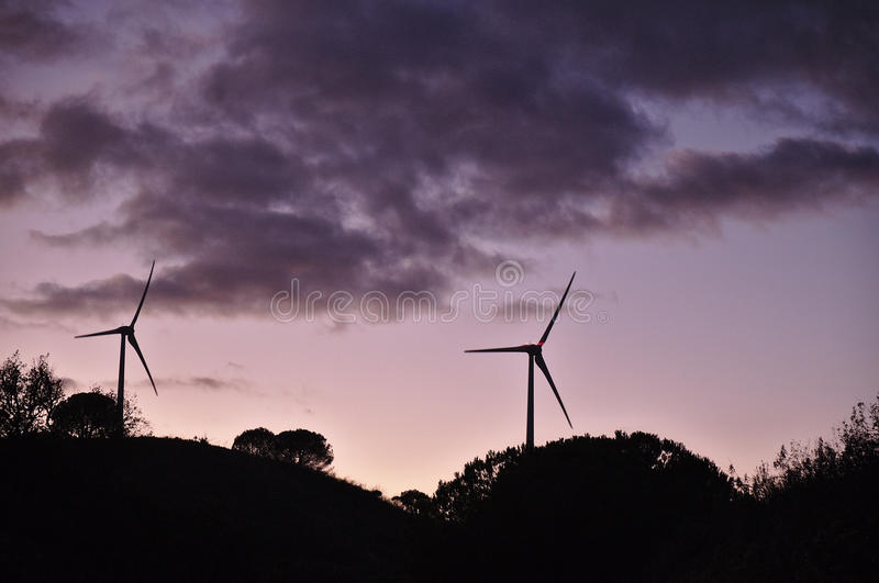 Wind turbines during dusk with clouds. Clean energy industries royalty free stock image