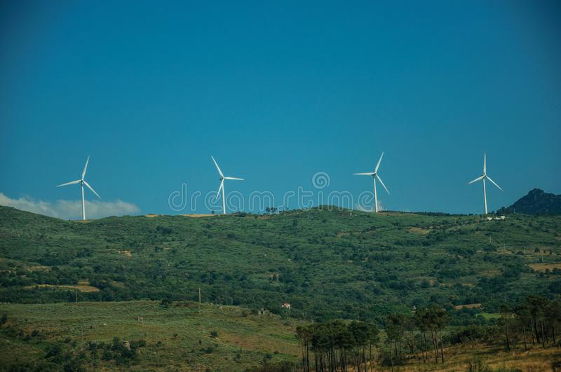 Wind turbines for electric power generation on hill. Some wind turbines for electric power generation on green hilly landscape with rocks, in a sunny day at royalty free stock photos