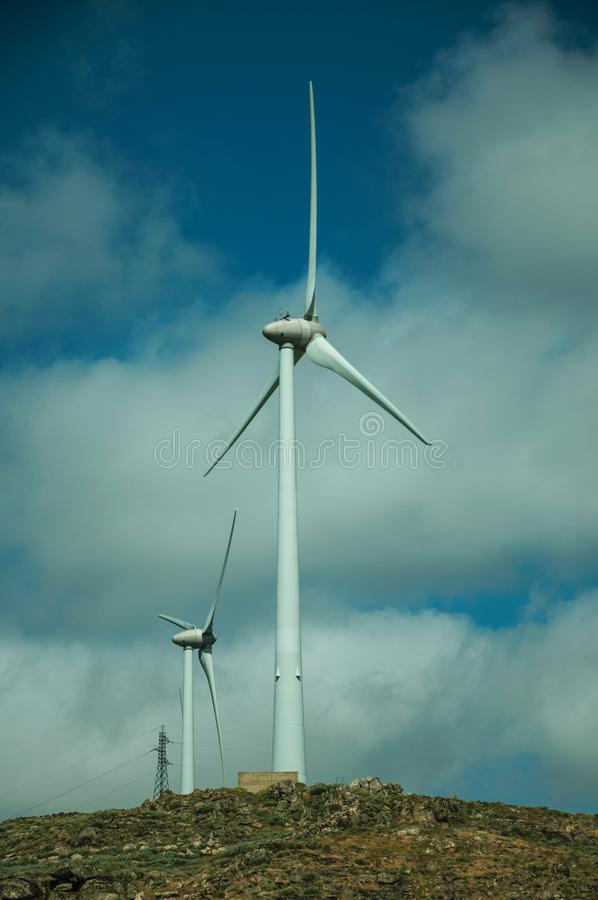 Wind turbines for electric power generation over hills. Wind turbines for electric power generation over green hilly landscape with rocks, in a sunny day near stock image