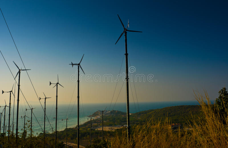 Wind turbines farm on the island. Wind turbines farm with a sunset, Pattaya Thailand stock images