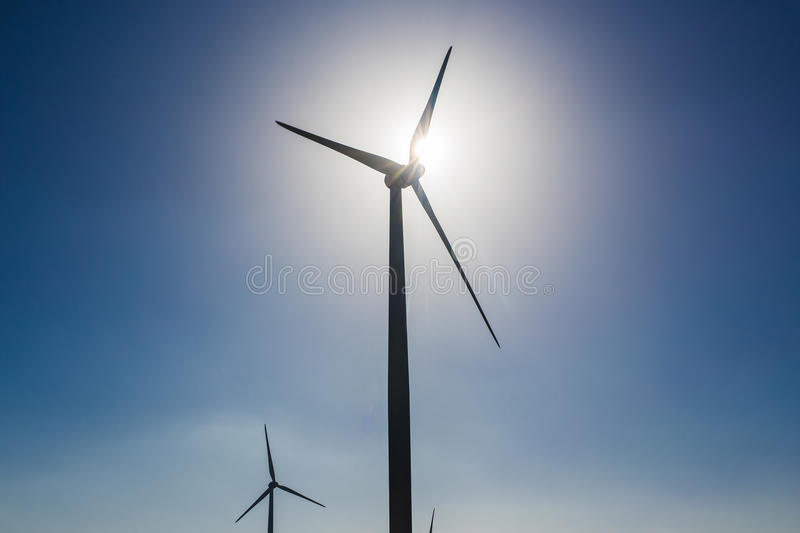 Wind turbines generating electricity with blue sky - energy conservation concept stock photos