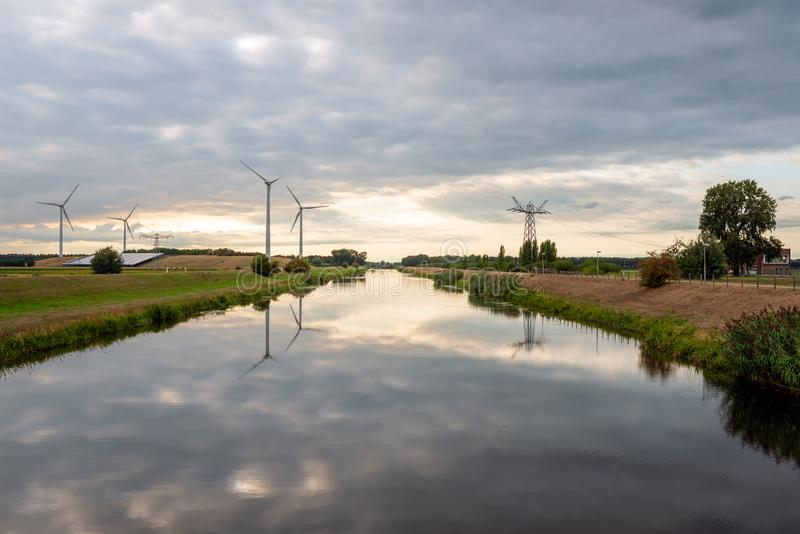 Wind turbines and high voltage pylons reflected in the water. Wind turbines and high voltage pylons reflected in the mirror smooth water surface. Solar panels stock images