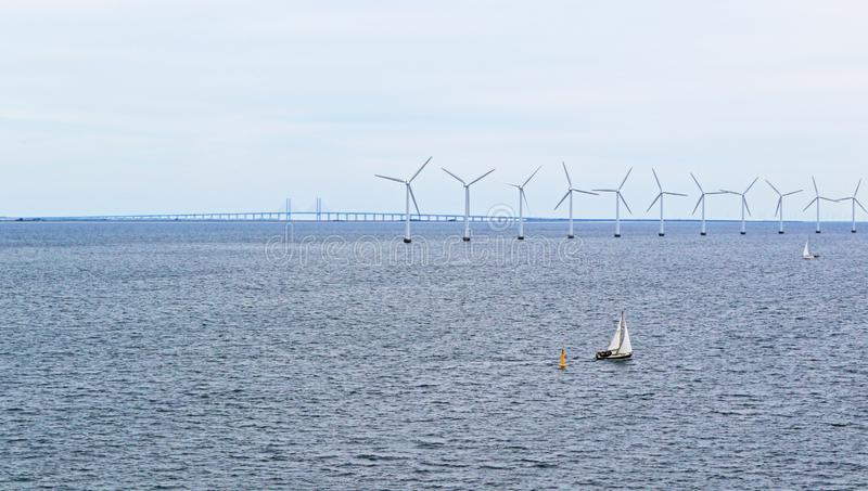 View of Baltic Sea wind park and Øresund Bridge. Wind turbines of Lillgrund Wind Farm -located about 10 km off the coast of southern Sweden, just south of the royalty free stock image