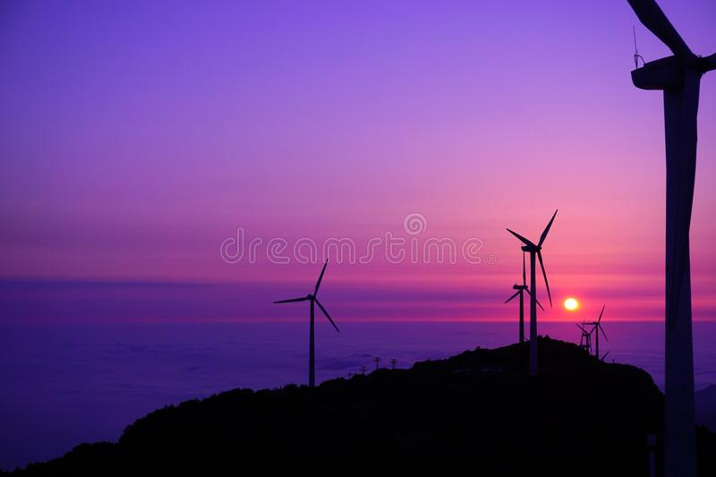 Wind turbines on the mountains at sunset. The wind turbines on the mountains at sunset are photoed when I have traveled on a high mountain stock images