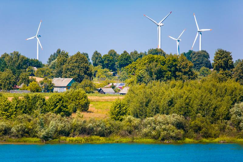 Wind turbines near small village. Renewable energy source concept. Rural landscape royalty free stock images