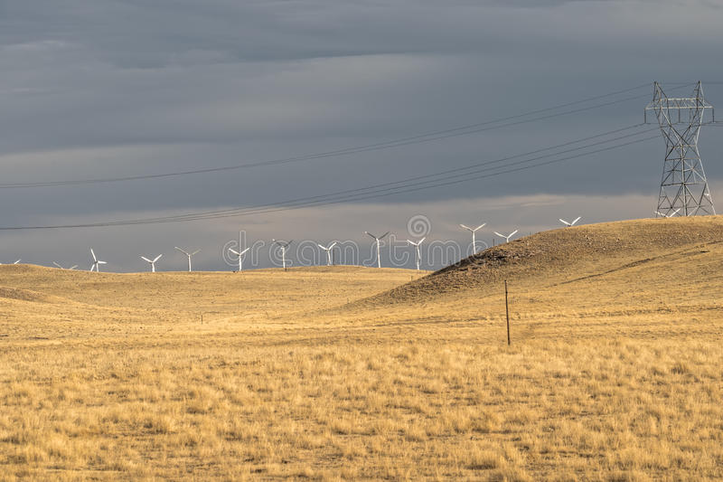 Wind turbines and power line in yellow field, meadow, before rain. Wind farm. USA royalty free stock photo