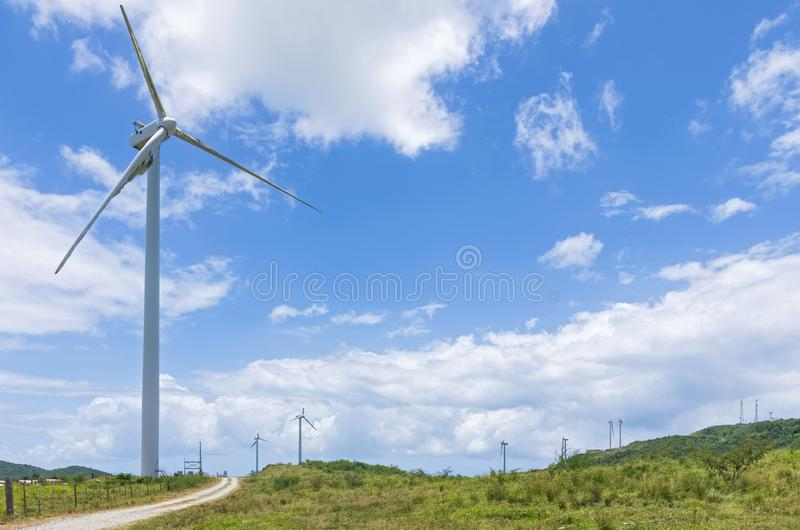 Wind turbines in Puerto Rico. Wind turbines on a wild landscape of Puerto Rico with narrow road running close to nearest turbine royalty free stock images