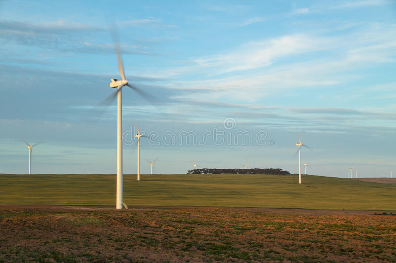 Wind turbines rotating in open farm land stock image