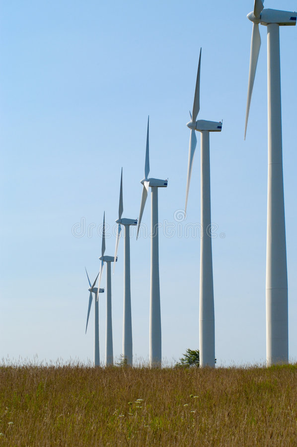 Wind turbines in a Row. Line of wind turbines extending to horizon of blue sky on a wind farm royalty free stock photography