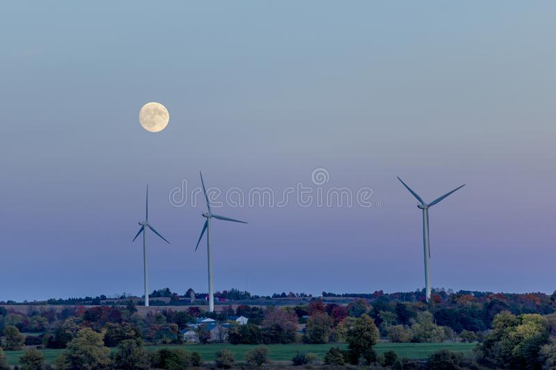 Wind turbines at dusk with a full moon royalty free stock photography