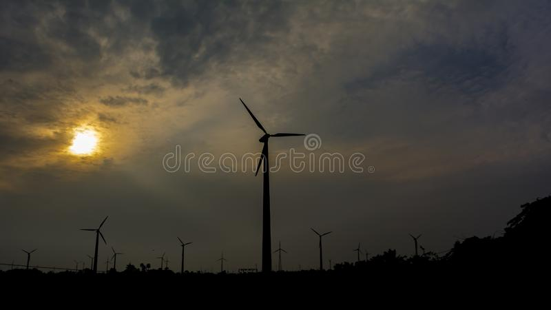 Wind Turbines Silhouette on a Sunset. A powerful picture displaying how true development can happen in an eco-friendly way. Picture showing palm trees and dense royalty free stock image