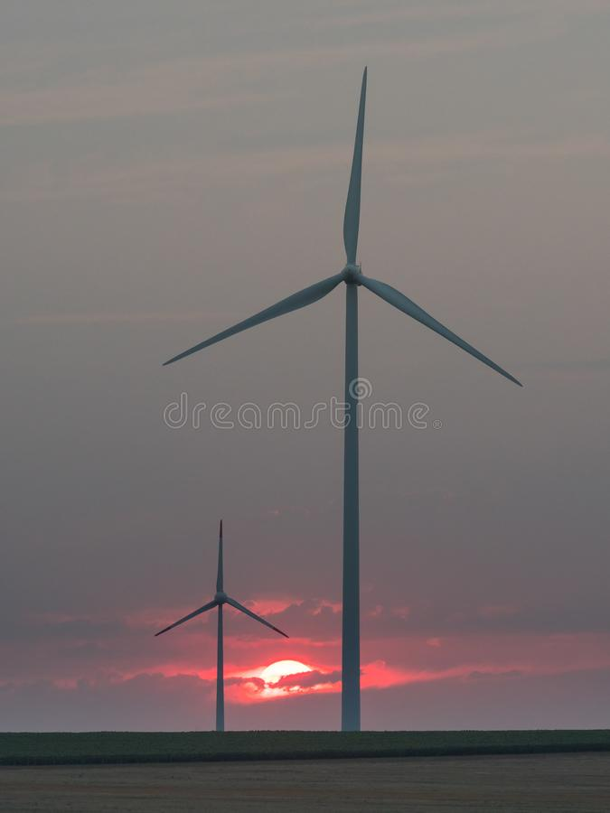 Wind turbines silhouettes in the setting sun royalty free stock image