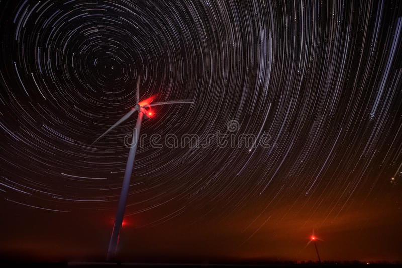 Wind turbines with stars trails royalty free stock image