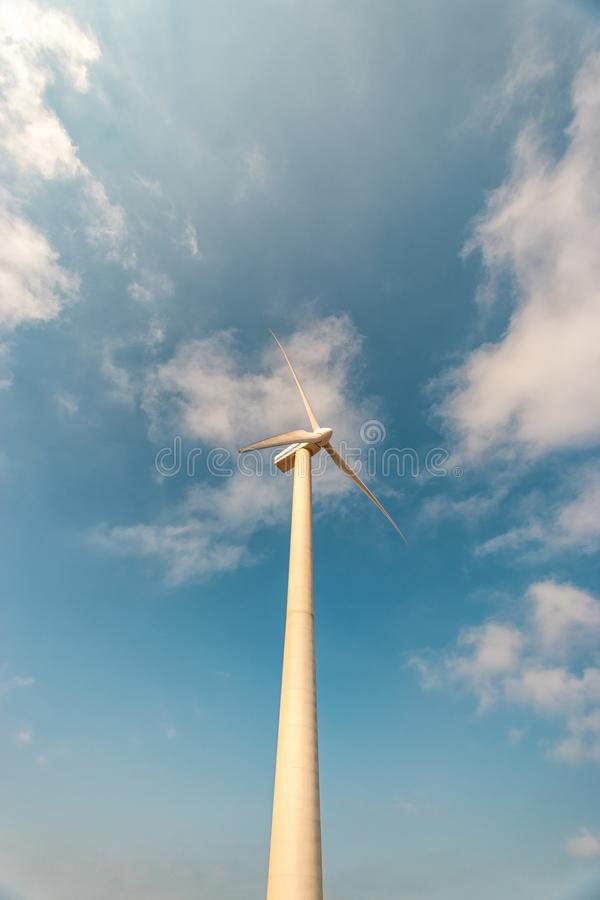 Wind turbines on a sunny day on sky background. Green energy generation concept stock photo