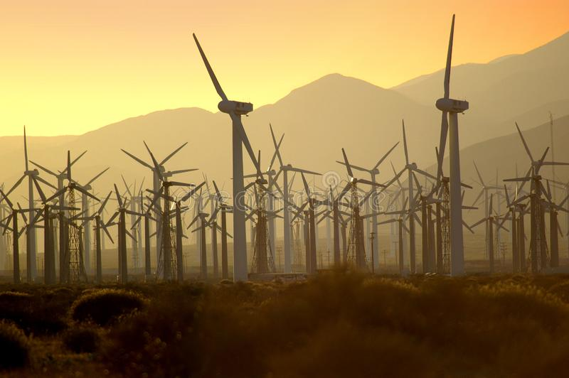 Wind turbines at sunset generating power as a fire is out of control burning nearby Palm Springs, California. royalty free stock photo
