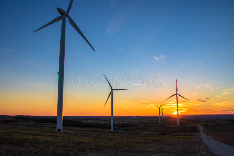 Wind Turbines Sunset. Landscape photo of the sun setting behind multiple Wind Turbines royalty free stock photos