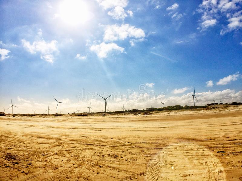 Wind turbines and the beach. Wind turbines to generate clean energy to the planet royalty free stock image