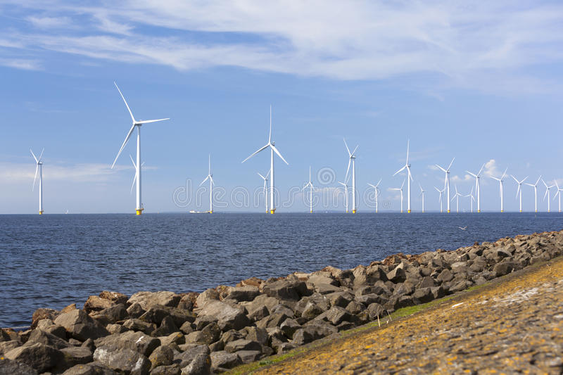 Wind turbines in water of ijsselmeer off the coast of flevoland. With blue sky in the netherlands royalty free stock photos