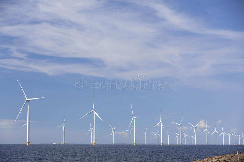 Wind turbines in water of ijsselmeer off the coast of flevoland. With blue sky in the netherlands stock photo