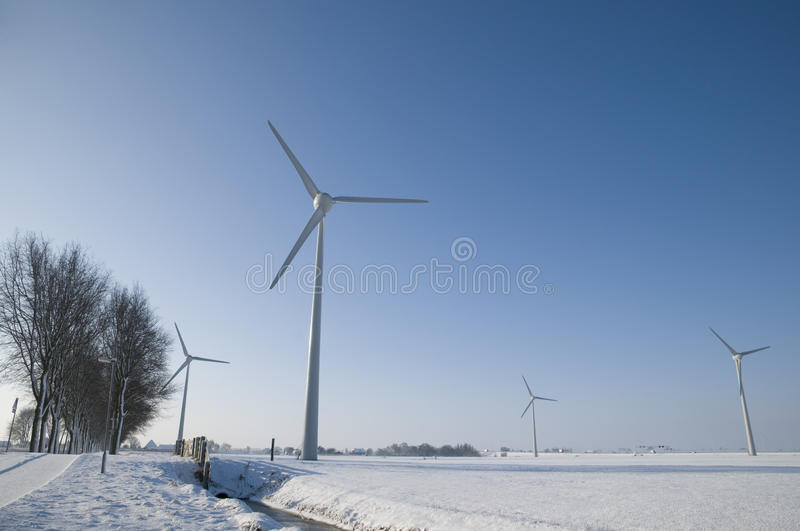 Wind turbines in winter landscape. Multiple wind turbines in winter landscape with blue sky royalty free stock images