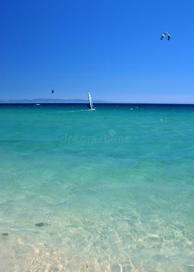 Wind- und Drachen-Surfer im Kristall - freies Meer mit hellem sonnigem blauem Himmel. stockfotografie