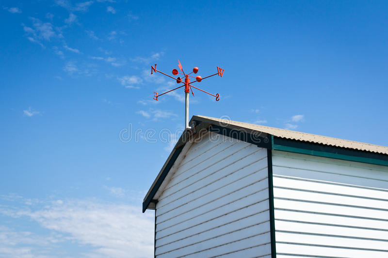 Wind vane. Red wind vane at the roof top stock photography
