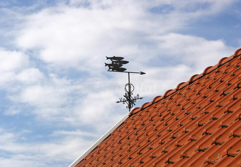 Wind vane with four fishes. On a tiled roof, Arild, Sweden stock image