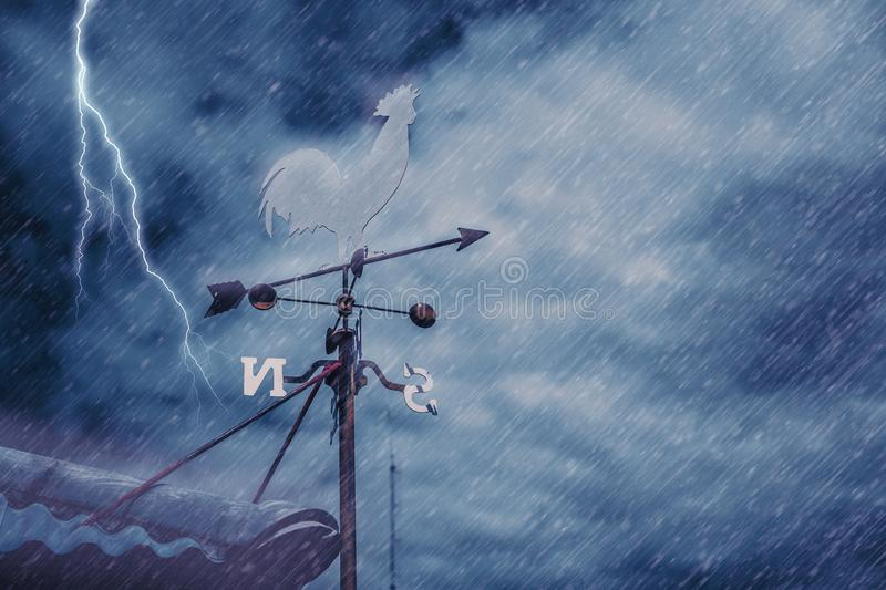 Wind vane on house roof with background of storm raining stock photos