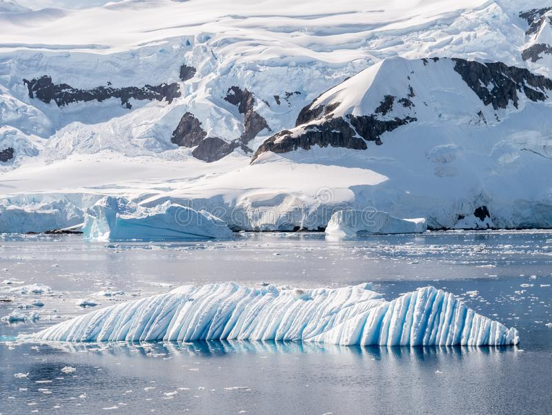 Wind and water sculpted iceberg drifting in Andvord Bay near Neko Harbor, Antarctic Peninsula, Antarctica. Wind and water sculpted iceberg floating in Andvord royalty free stock photography