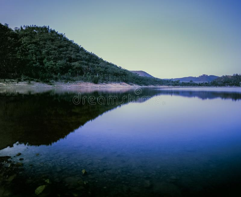 Hill and landscape reflecting in lake Windamere Dam New South Wales Australia at blue hour stock images