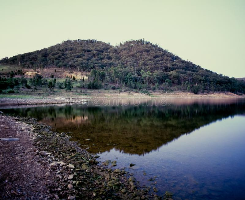 Hill and landscape reflecting in lake Windamere Dam New South Wales Australia at blue hour stock photos