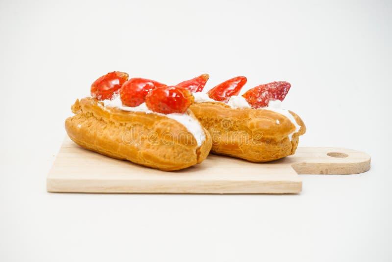 Windbeutel mit Erdbeerscheiben auf dem Kuchen lokalisiert auf weißem Hintergrund stockfotografie