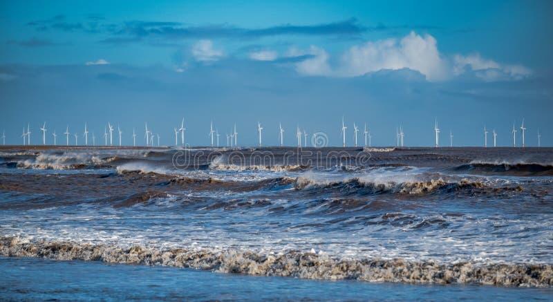 Windblown golven die op de kust met een windlandbouwbedrijf breken op de horizon royalty-vrije stock fotografie