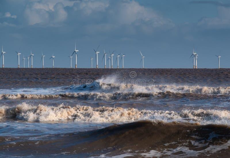 Windblown golven die op de kust met een windlandbouwbedrijf breken op de horizon stock afbeelding
