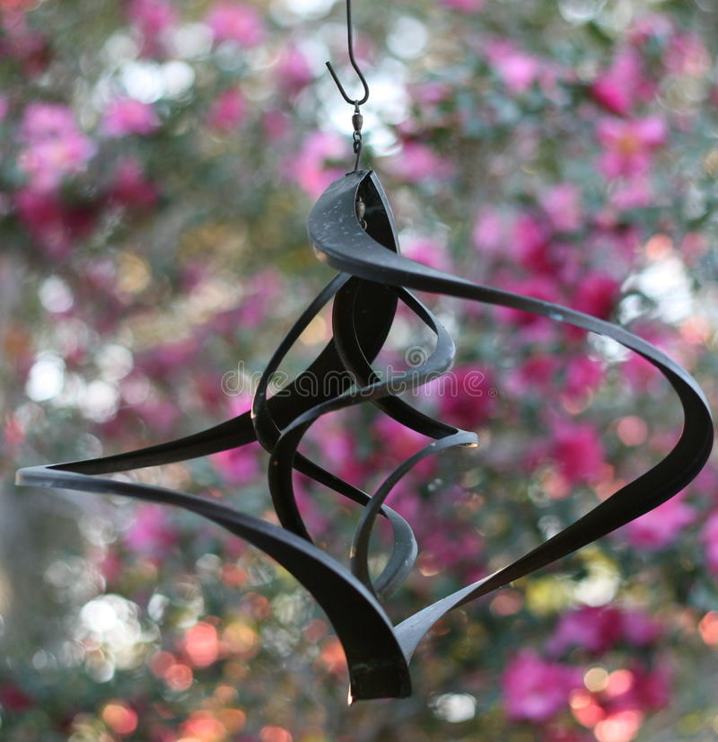 Windchime Against Pink Camelia Backdrop Stock Images