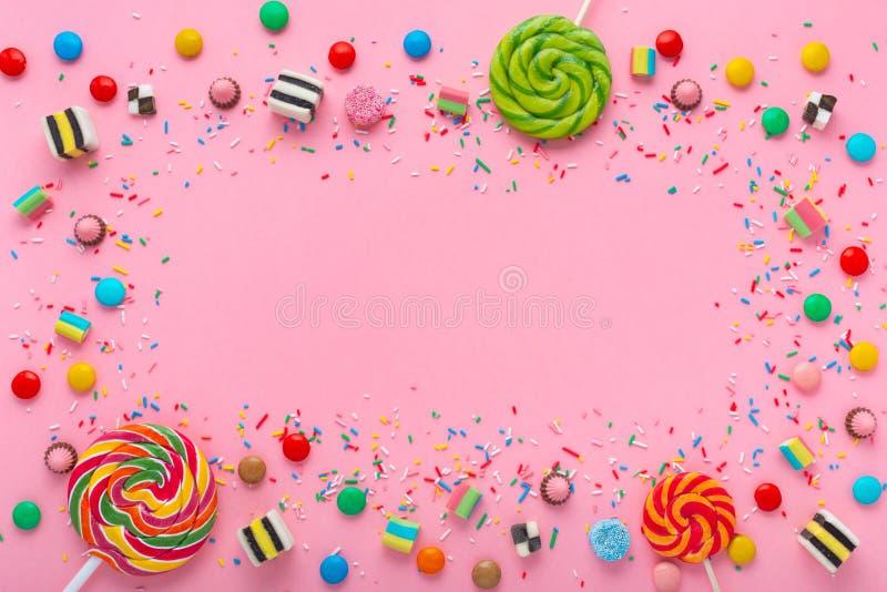 winden Sie Hintergrund mit Zusammenstellung von bunten Karamellsüßigkeiten mit Gelee und besprüht über Rosa und Raum für Ihr lizenzfreies stockbild