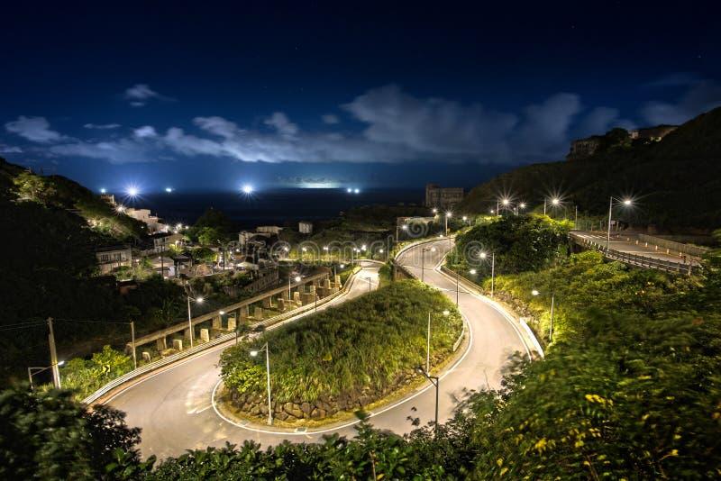Windende die bergweg bij nacht wordt aangestoken stock afbeeldingen