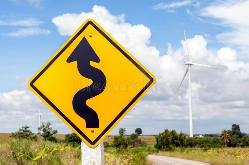 Windende verkeersteken met windmolenachtergrond in windlandbouwbedrijf stock foto