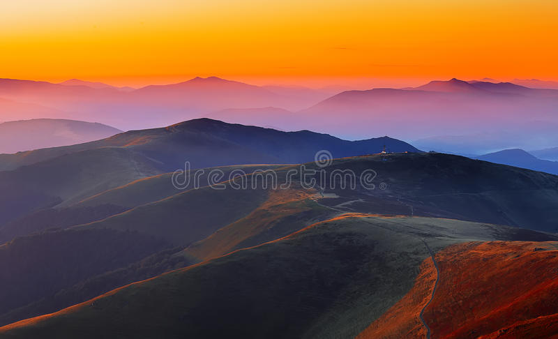 Windende weg door weiden van bergketen bij zonsondergang royalty-vrije stock foto's