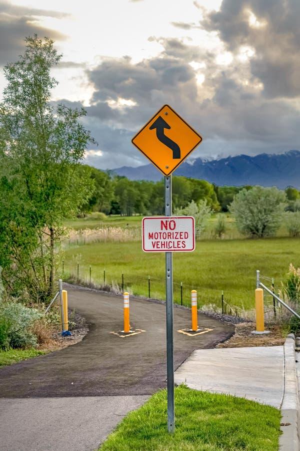 Windende Weg vooruit en Geen Gemotoriseerd Voertuigenteken tegen aardachtergrond stock foto's
