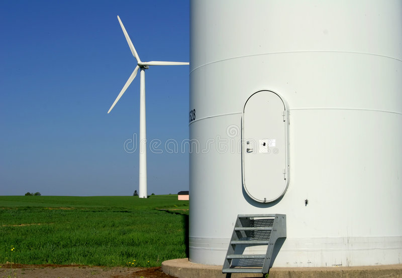 Windenergy 5. Modern wind energy plant behind the entrance of an other plant stock photos