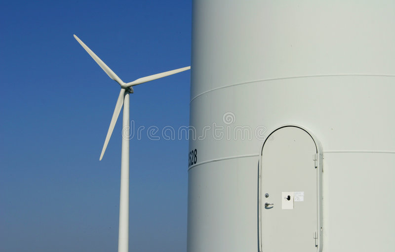 Windenergy 6. Modern wind energy plant behind the entrance of an other plant royalty free stock photos