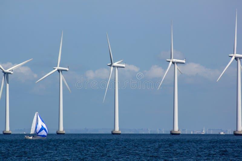 Windfarm a pouca distância do mar sustentável com veleiro imagem de stock