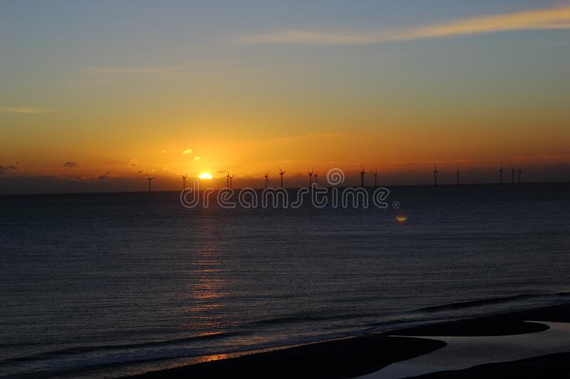 Windfarm silhouette at sunset stock photo